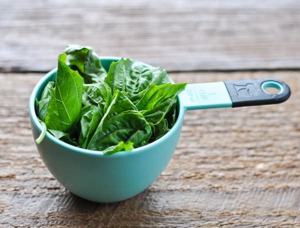 Fresh basil leaves in a measuring cup