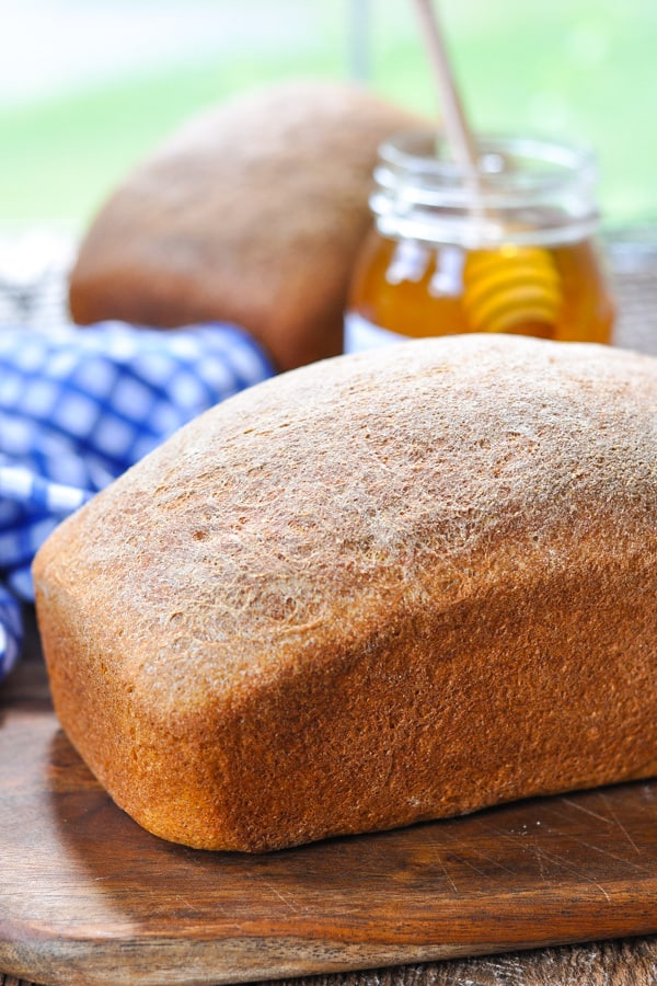 Two loaves of homemade whole wheat bread on cutting boards with honey in the background