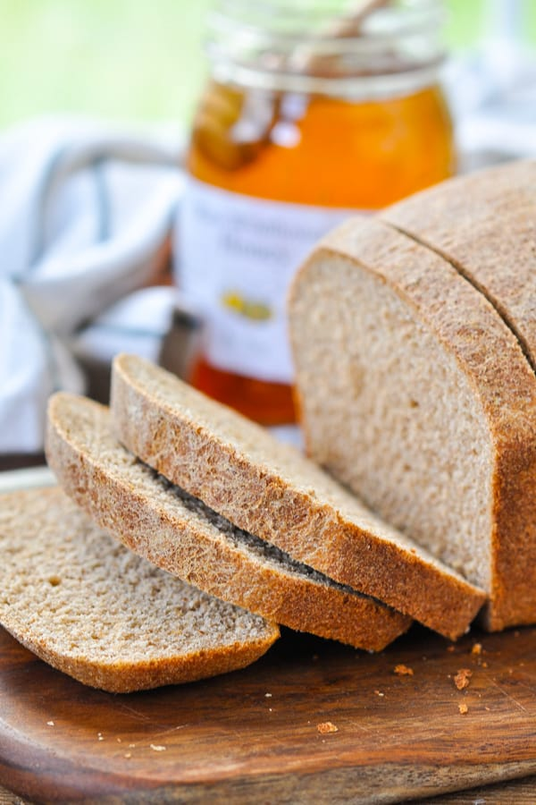 Close up side shot of a loaf of homemade honey wheat bread with a jar of honey in the background