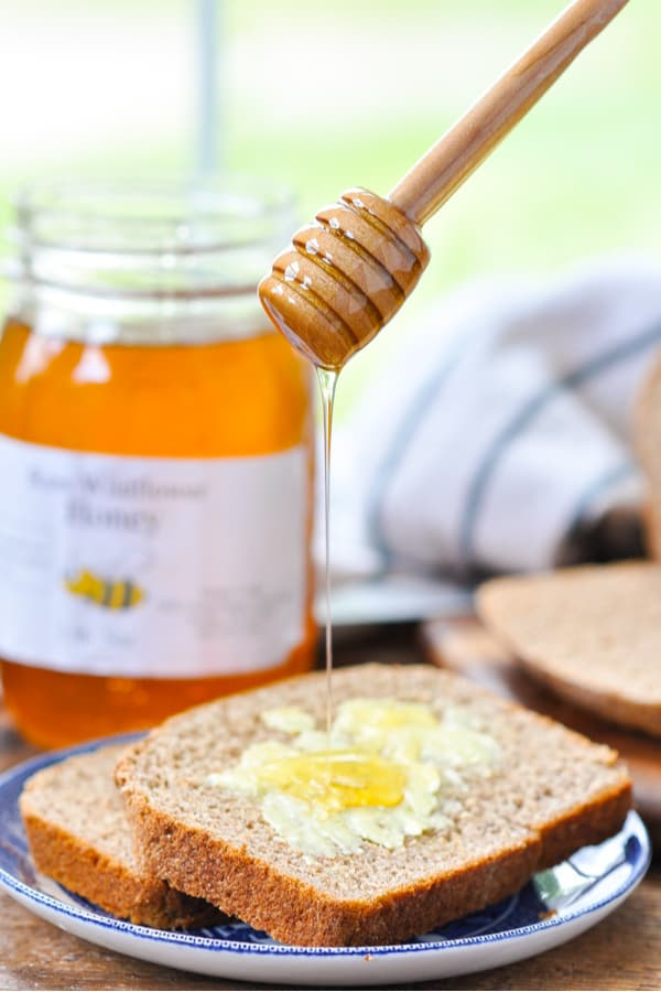Drizzling honey on a slice of homemade wheat bread spread with butter