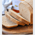 Sliced loaf of honey wheat bread with title text below the photo