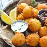 Close side shot of a tray of homemade Southern hush puppies served with lemon wedges