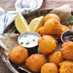 Side shot of hush puppies served with lemon wedges and two different types of dip