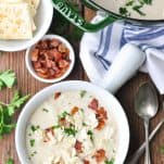 Overhead image of a bowl of new england clam chowder with bacon and parsley on top on a wooden table