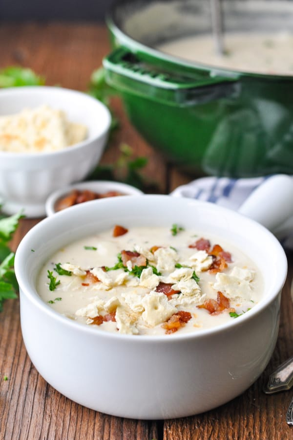 Close up front shot of a white bowl full of New England clam chowder with a bacon and parsley garnish