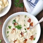 Close overhead image of a bowl of New England clam chowder on a wooden table