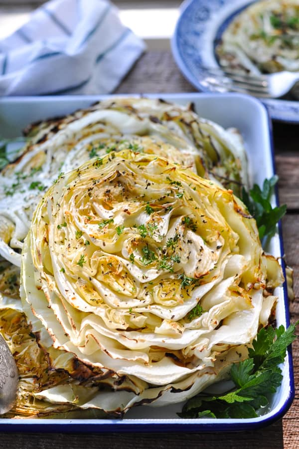 Front shot of garlic roasted cabbage wedges on a blue and white serving tray