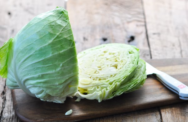 Slicing a head of cabbage on a wooden cutting board