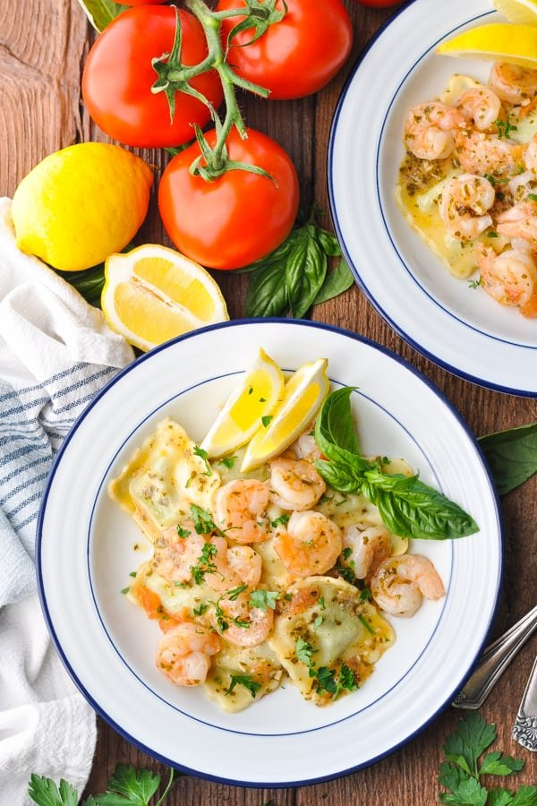 Overhead shot of two bowls of shrimp with ravioli in a pesto sauce
