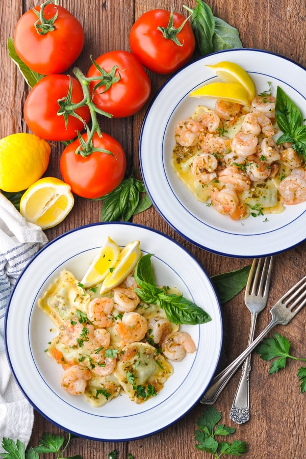 Overhead image of two bowls of shrimp and ravioli on a wooden table
