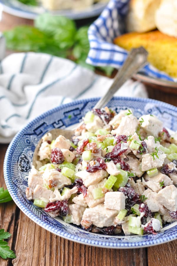 Front shot of a bowl of homemade chicken salad with grapes or cranberries and a basket of cornbread and rolls in the background