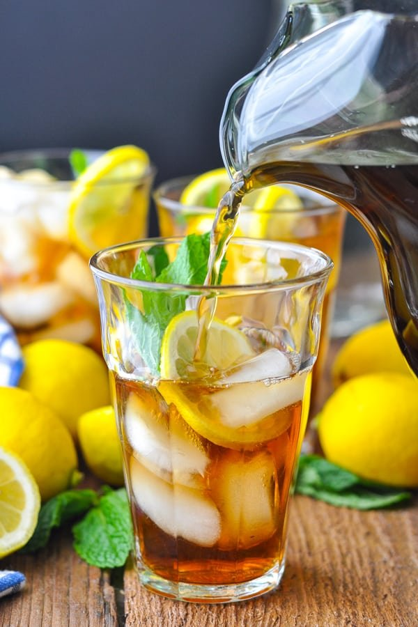 Pouring a glass of sweet tea over ice with lemon and mint