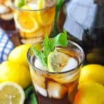 Two glasses of sweet iced tea on a wooden table with lemons