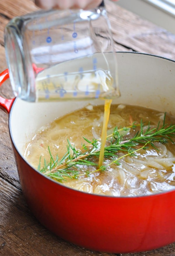 Pouring apple cider into a dutch oven for braised pork