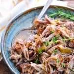Front shot of shredded pork in a bowl with drippings