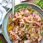Close up overhead shot of a bowl of cider braised pulled pork with herbs
