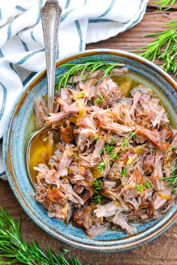 Close overhead image of a bowl of braised pork shoulder garnished with fresh herbs