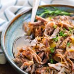 Front side shot of a bowl of shredded pork with silver serving spoon