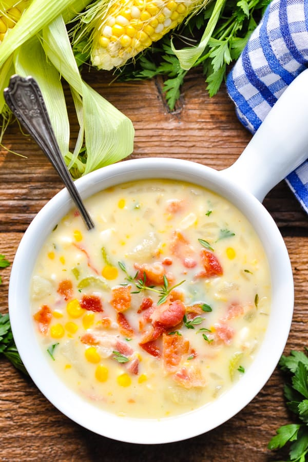 Overhead shot of fresh corn chowder on a wooden table
