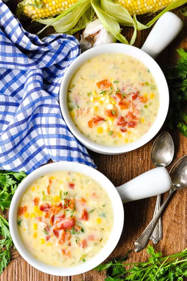Overhead shot of two bowls of creamy corn chowder on a wooden table