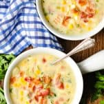 Overhead shot of corn chowder bowls on a table with fresh parsley nearby