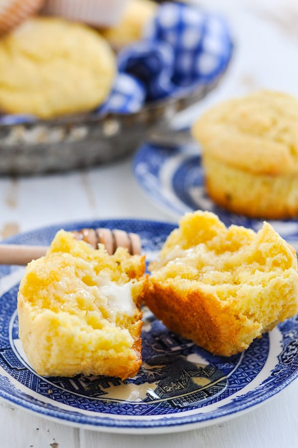 Side shot of a cornbread muffin cut in half on a plate with butter and honey