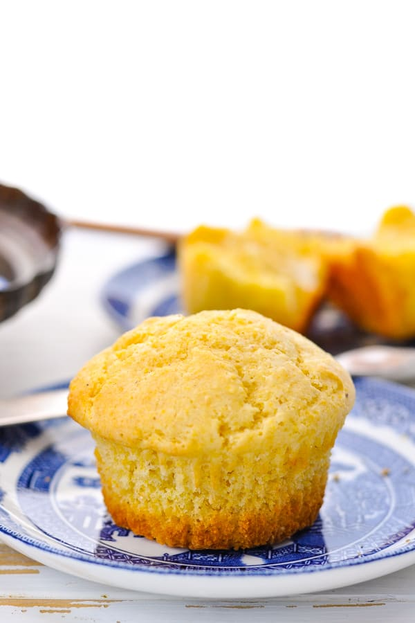 Front shot of a corn muffin on a blue and white plate with another muffin on a plate in the background
