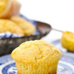 Single corn muffin on a plate with a basket of muffins in the background