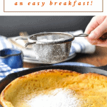 Sprinkling powdered sugar on a dutch baby pancake with text title at the top