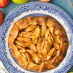 Overhead image of an apple galette on a blue table