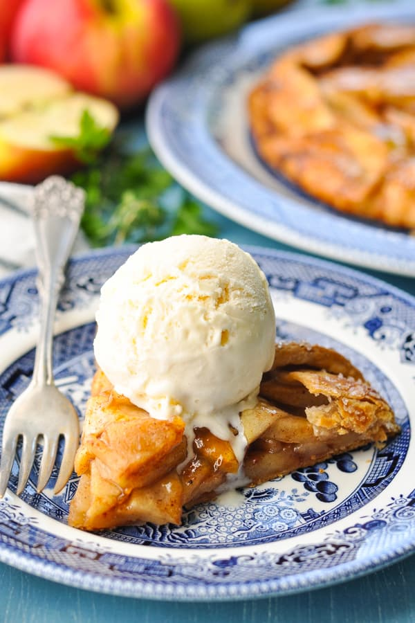 Front shot of a slice of apple galette topped with vanilla ice cream