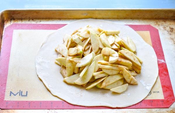 Process shot of assembling an apple galette
