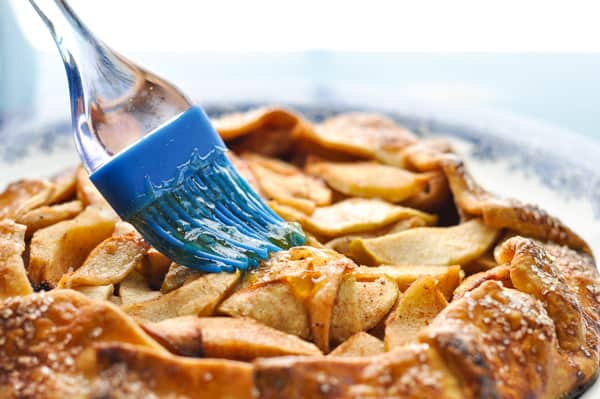 Brushing apricot jam on an apple galette