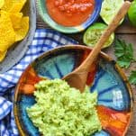 Overhead shot of a bowl of guacamole served with chips and salsa