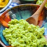 Side shot of an easy guacamole recipe served in a bowl with a wooden spoon