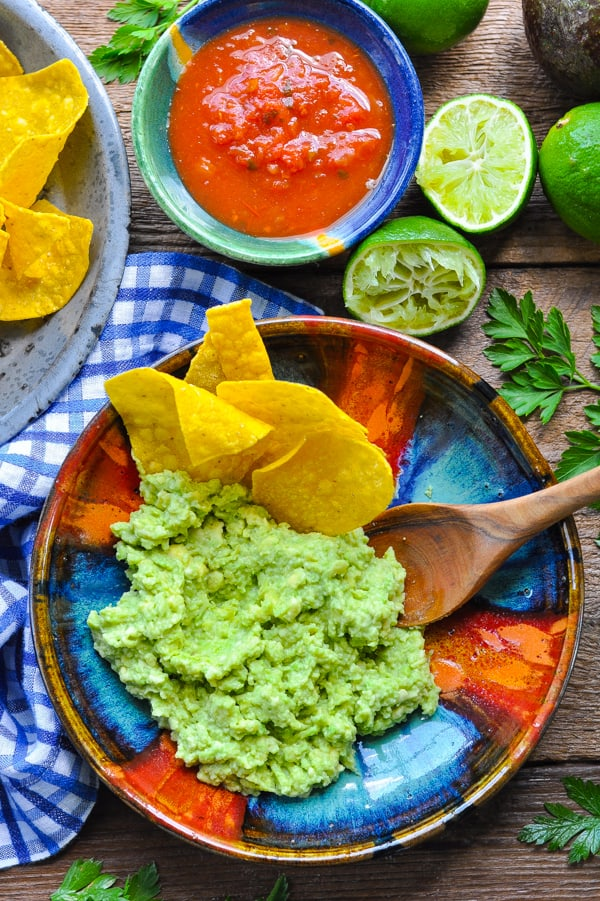 Overhead shot of tortilla chips and a wooden spoon in a bowl of easy guacamole