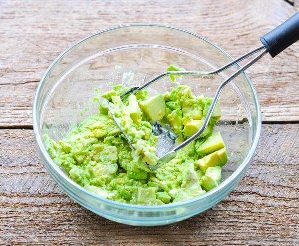 Mashing avocado in a glass mixing bowl