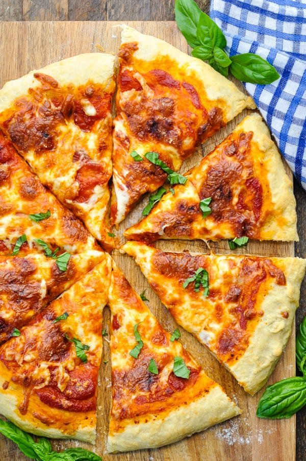 Overhead image of homemade cheese pizza garnished with fresh basil
