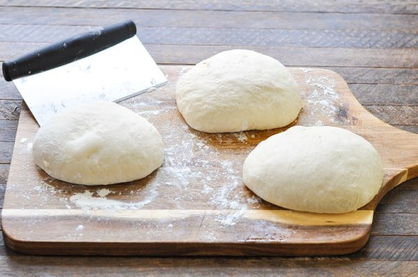 Three balls of easy pizza dough on a wooden cutting board