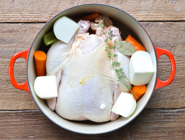 Whole chicken in a Dutch oven with vegetables and water
