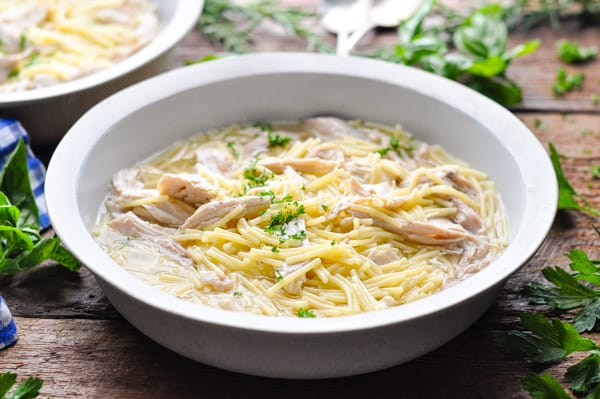 Horizontal shot of a bowl of farmhouse chicken and noodles with parsley garnish