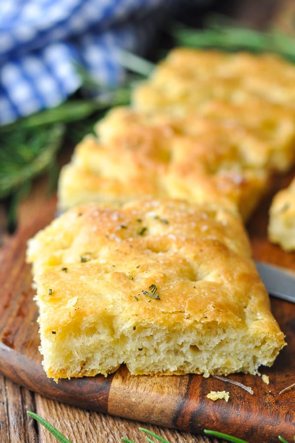 Close up shot of a slice of focaccia bread on a cutting board