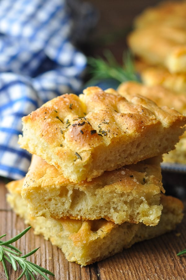 Homemade focaccia bread recipe sliced into squares and stacked on top of each other