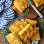 Overhead image of focaccia bread recipe served on a blue and white plate on a wooden table