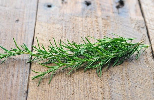 Fresh rosemary sprigs on a wooden table