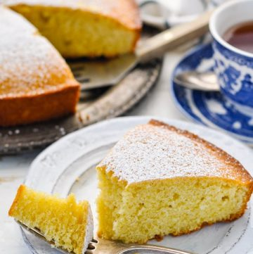 Front shot of a slice of French farmhouse breakfast cake served on a white plate with the rest of the cake in the background