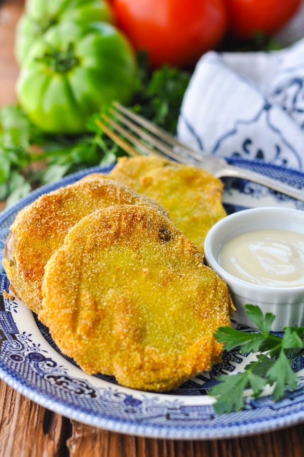 Side shot of three fried green tomato slices on a plate with parsley and dip