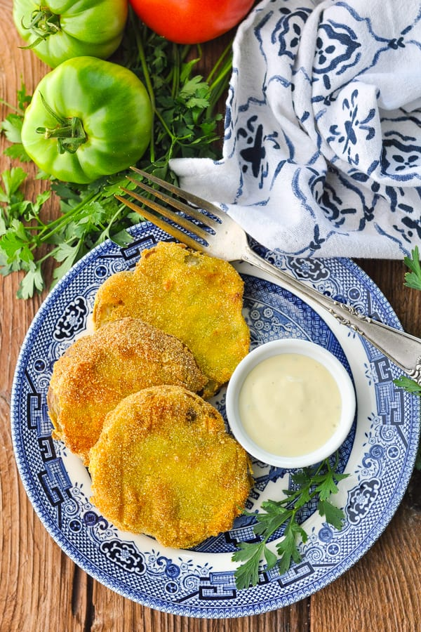 Overhead shot of fried green tomatoes on a wooden table with a blue and white towel nearby
