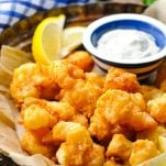Side shot of an easy fried shrimp recipe on a table with a blue and white checked towel in the background