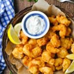 Overhead image of a tray of fried shrimp served with lemon and tartar sauce